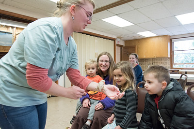 04/11/18  Wesley Bunnell | Staff  Animal care staffer and educator Meaghan Jameson holds a gecko during an animal class at the New Britain Youth Museum at Hungerford Park on Wednesday afternoon. Looking on are Karen Bennett, L, with her children Theodore, age 2, and Johannha, age 4. Dennis Archambeault, age 5, sits on the R.