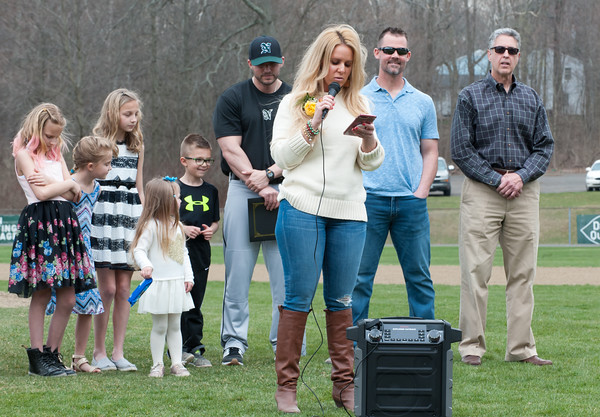 04/13/18 Wesley Bunnell | Staff Daughter of Paul Baretta Andrea Baretta-Maule, gives a speech while in the background her husband and assistant coach at NW Catholic Jason Maule stands with the couples two children Nerea, 2nd from L, and Trey, 5th from L, David Swanson, 2nd from R, and Mayor Mark Kaczynski, R, during the dedication of the Paul Baretta baseball field. The Town of Berlin dedicated Paul Baretta Field at Percival Park on April 13th before the Berlin High School baseball game vs Northwest Catholic.