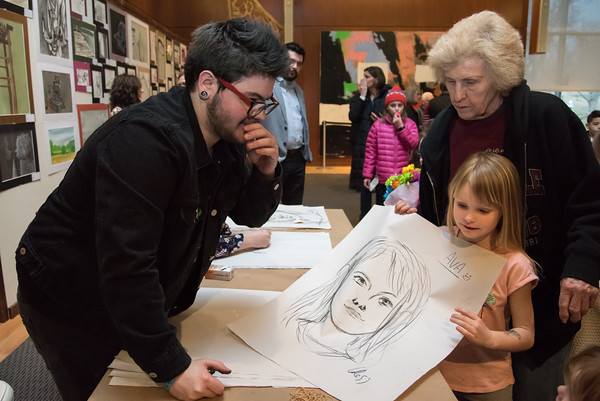 04/17/18 Wesley Bunnell | Staff Berlin High School senior Graham Damien Ross hands an original drawing of Ava Matteson, age 6, to her as she stands next to her grandmother Barbara Dufresne. Ava has artwork on display as a student of Griswold Elementary School. An opening reception was held Tuesday night at the New Britain Museum of American Art featuring creative artwork from Berlin Public School students.