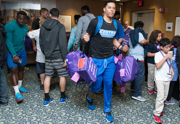 04/27/18 Wesley Bunnell | Staff The CCSU Ana Grace Project held Love Wins: Finish the Race on Friday to give young middle school students from across New Britain a college experience for the day and have them explore their possibilities. CCSU volunteers included many student athletes. CCSU basketball player Tyson Batiste carries backpacks full of sneakers, pencils, a yo yo and water bottle out to the students.