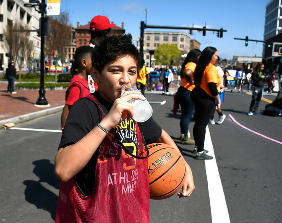 4/28/2018 Mike Orazzi | Staff Ricardo Almodovar takes a drink to cool off during the annual Hoops for Homeless in downtown New Britain.