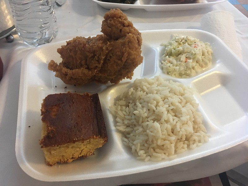 A styrofoam tray on a white tablecloth table has a square of cornbread, a pile of white rice, coleslaw, and a piece of fried chicken