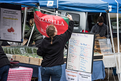 A vendor hoists a sign to attract buyers to try a taste of her Mozzarella de Buffalo cheese. [Bill Giduz photo]