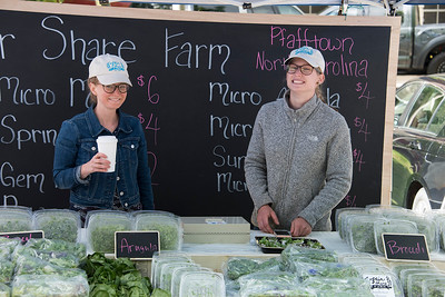 In between the Arugula and Broccoli, these proprietors ward of the chill at their vegetable stand. [Bill Giduz photo]