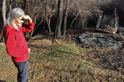 Katia Wilder looks over a 2,400-gallon water tank that melted when the Camp Fire reached her property last November. (Steve Schoonover -- Chico Enterprise-Record)