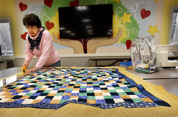 BRYAN EATON/Staff Photo. Judy Marcin of Amesbury squares off her quilt for the binding at the Hilton Senior Center in Salisbury on Tuesday afternoon. The group meets once a week to work on their quilts that they donate to local charitable organizations.