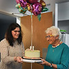 BRYAN EATON/Staff Photo. Theresa Woodbury, director of the West Newbury Council Aging, hands West Newbury resident Florence Zuker, who turned 100 this weekend, a birthday cake at a small party.