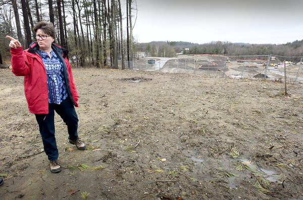 BRYAN EATON/Staff Photo. Kathy Kodwyck talks about her unhappiness with the housing project at Bailey's Pond in Amesbury while standing in her back yard which was marred by construction of retaining walls below.