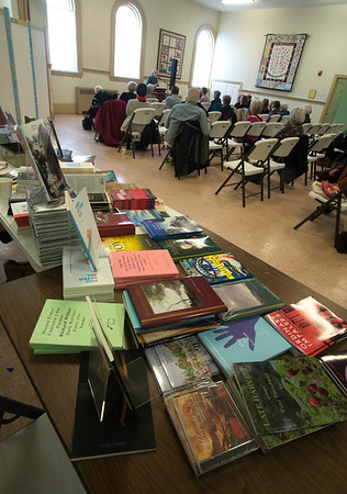 JIM VAIKNORAS/Staff photo Poetry books for sale cover a display table as  Maryann Corbett does a reading at the Central Congregational Church during the annual Newburyport Literary Festival Saturday.