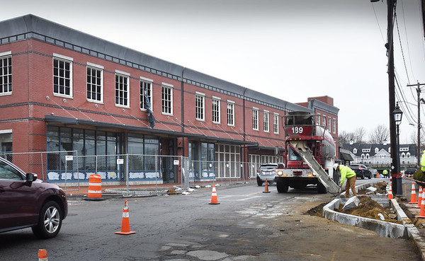 BRYAN EATON/Staff Photo. Concrete is poured into new curbing across from the new parking garage on Merrimac Street in Newburyport on Tuesday afternoon.