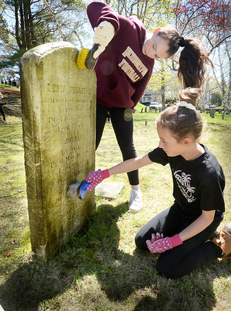 BRYAN EATON/Staff Photo. Using a special solution Hayleigh Lawrence, top, and Haley Mann, both 13, clean the grave of Dennis Sullivan in the Old Hill Burying Ground on Thursday afternoon under the direction of Ghlee Woodworth. The seventh-graders at the Nock Middle School in Newburyport held a community service week, and cleaning, repairing headstones and general cleanup of the Newburyport Cemetery was one of their projects.