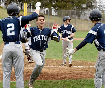 BRYAN EATON/Staff Photo. Triton's Jack Tummino gets a homer on a hit by Jared Berardo which was dropped.