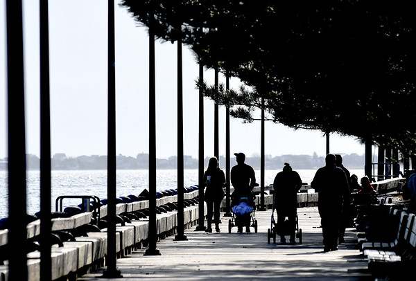JIM VAIKNORAS/Staff photo Walkers are cast in silhouette as the sun shines on a warm spring morning Sunday.