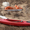BRYAN EATON/Staff Photo. Three watercraft, the kayak filled with rainwater, sit idle in the grassy dunes on Plum Island. The weather does warm up for the weekend, though it may be still too early for water activity on the Merrimack River.