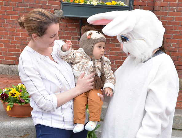 JIM VAIKNORAS/Staff photo Benjamin Wilson, 8 months, checks out the Easter Bunny with his mom Kristin Saturday morning in Market Square in Amesbury. The big bunny was there to pose for photos and collect donations for the Kim Gilbert Owen Memorial Scholarship, names for Kim who passed away last year.