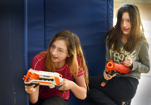BRYAN EATON/Staff Photo. Sisters Katrina Glosson, 12, left, and Amber, 13, take cover behind gymnastic mats during a game of Nerf Battles at the Newburyport Rec Center at the Brown School. The center is open for grades six and above from 4-6:00 p.m. Tuesday through Thursday this school vacation week.