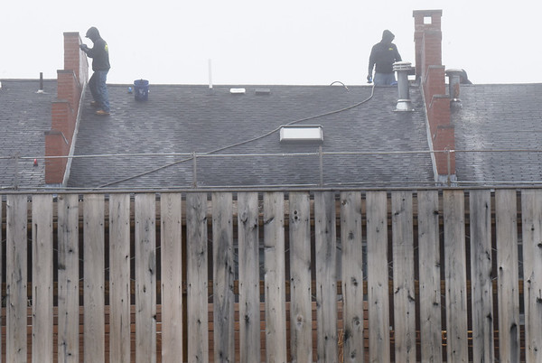 BRYAN EATON/Staff Photo. Roofers continue the pointing of the firewalls and chimneys on the East Row Block in downtown Newburyport in the misty weather on Monday morning before the rain came later in the afternoon. The roof replacement is planned on being complete before Memorial Day.