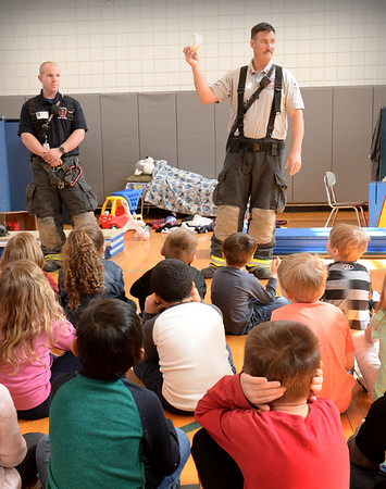 BRYAN EATON/Staff Photo. Students cover their ears as Lt. Adam Foss activates a smoke detector.