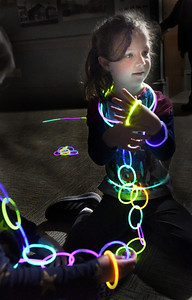 BRYAN EATON/Staff Photo. Faith Ann Page, 6, of Newburyport creates a chain of glow sticks with friends in the darkened program room at the Newburyport Public Library late Wednesday morning. It was one of the events at the library for school vacation week, another one in the afternoon being the Great Oreo Cookie Tasteoff.