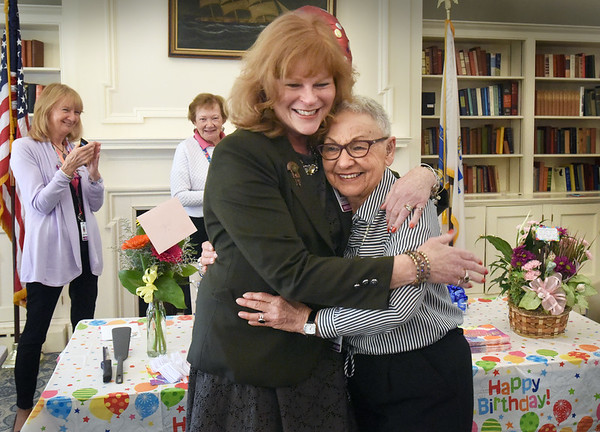 BRYAN EATON/Staff Photo. Anna Jaques Hospital Director of Volunteer Services Cheryl Satryb, gets a hug from volunteer Geri Buzzota, right, at a surprise 90th birthday attended by fellow volunteers and hospital staff including Mark Goldstein, president and CEO. Geri is a gift shop volunteer--and will continue to be--and comes twice a week and has been with the hospital for ten years, ten months, with 1,900 hours of service and she also serves on the AJH Aid Association Board.