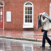 BRYAN EATON/Staff Photo. Kathleen Pasquina of Newburyport uses her coat as an impromptu umbrella crossing State Street in downtown Newburyport as she and others were caught in the second round of rain on Monday afternoon. Rain is forecast to return possibly Friday night into Saturday.