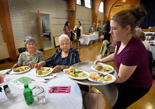 BRYAN EATON/Staff Photo. Paulina Brunelle serves lunch of chicken Florentine, angel hair past and steamed vegetables to volunteers Susan Dodge, left, and Joanne Gaynor. They were at Volunteer and Sponsor Appreciation Luncheon by the Amesbury Council on Aging held at Holy Family Parish Hall on Thursday afternoon.