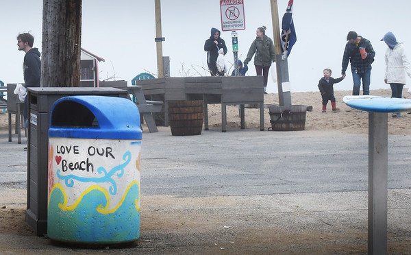 BRYAN EATON/Staff Photo. The art on the trash barrel says it all as people come back with bags of litter collected at Salisbury Beach on Monday morning. They were part of the Earth Day Beach Cleanup sponsored by the Ground Swell Surf Cafe.