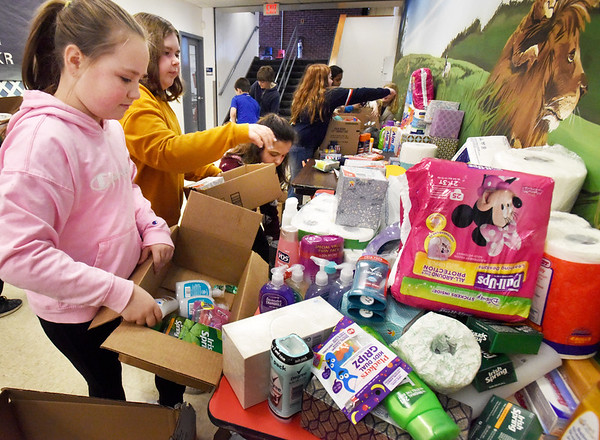 BRYAN EATON/Staff photo. Amesbury's Cashman School student council organized a toiletry drive for Our Neighbors' Table. Here members, from left, Carrington McCarthy, Keira Steinel and Lavinia Minkowski, all, 10, and the rest of the members loaded up the goods for the awaiting van on Tuesday morning.