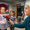 BRYAN EATON/Staff Photo. Avery Couture, 5, left,  Juliann Burnham, 5, and Alice Eduardo, 6, out of view, deliver flowers to Salisbury Elementary School nurse Terry Arsenault on Tuesday afternoon. The kindergartners in Aimee Farrell's class have a flower store every April and take turns putting together bouquets and delivering them to teachers and other staff to show their appreciation.