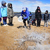 BRYAN EATON/Staff Photo. Johanna True from Mass Audubon's Joppa Flats Education Center throws a bucket of water, representing ocean waves, on a small sand dune second-graders from Burlington made and tried to reinforce with rocks and driftwood on the beach at Plum Island on Wednesday morning. In collaboration with the Burlington Science Center they were teaching the youngsters about the vulnerability of barrier beaches with the forces of wind and tides and they also planted dune grass which retains sand from being washed away.