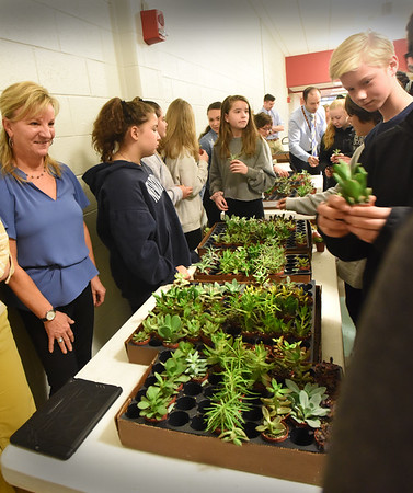 BRYAN EATON/Staff Photo. Susan Harvey, left, looks on as Nock Middle School students pick up small plants she brought for them to take home. Harvey, from Plantwerks in Salisbury, was at the Newburyport School on Tuesday for Earth Day and gave a presentation to students about the power of living plants in indoor spaces with the theme about biophilia and how plants help us live a healthier lifestyle in many ways (clean air, absorbtion of carbon-dioxide and natural anti-anxiety).