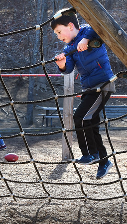 BRYAN EATON/Staff Photo. The windy weather didn't keep youngsters from hitting the playground at Amesbury Elementary School in the Youth Services afterschool program. Braden Bailey, 7, climbs the rope ladder after he and his friend had snacks inside.