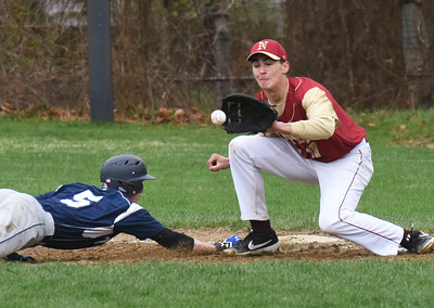 BRYAN EATON/Staff Photo. Triton's Tyler Godfrey makes it back to first as Newburyport's Parker McLaren waits for the throw.