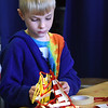 BRYAN EATON/Staff Photo. Jack MacDonald, 8, builds a shelter out of plastic plates, pipe cleaners, clothespins, and tape at the Newburyport Rec Center. He was in a science unit for school vacation activities where they pretended they were shipwrecked and swam to an island and built the shelters which could keep out the rain.