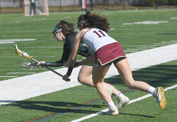 JIM VAIKNORAS/Staff photo Manchester-Essex player Brigit Edgerton fights for a loose ball with Bridget Lane at World War Memorial Stadium in Newburyport Thursday night.