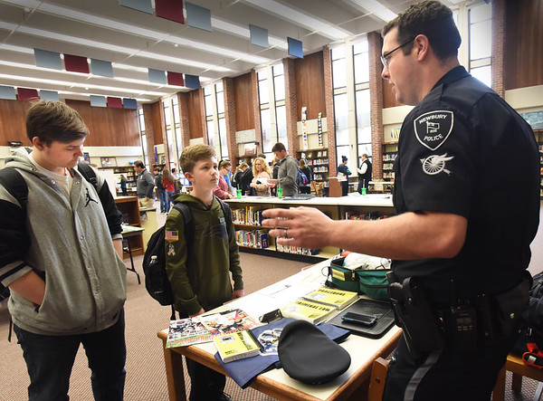 BRYAN EATON/Staff Photo. Zechariah LaPorte, 15, and Connor Noone, 14, listen to Newbury police officer and school resource officer John R. Lucey about a career in law enforcement. They were at the Vocational Career Fair at Triton Regional High School, the first the Byfield school has hosted.