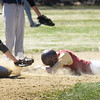 BRYAN EATON/Staff Photo. Thomas Murphy eats the dust on a double in action against Essex-Tech.