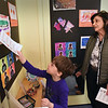 BRYAN EATON/Staff Photo. L. J. Gifford, 6, decribes his creations to his aunt, Janice Chiaradonna, during his classroom's art show at the Newburyport Montessori School on Wednesday morning. The young artists created different pieces of work using different techniques and media.
