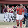 JIM VAIKNORAS/Staff photo Amesbury catcher Derek Beaupre retrieves his mask as Newburyport players celebrate a first inning run at 	Pettingell Park in Newburyport Friday.