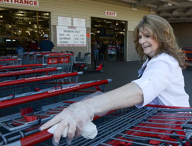 Belinda Padula smiles as she wipes down shopping carts with a disinfectant wipe at Costco on March 21 in Chico, California. (Matt Bates -- Enterprise-Record)