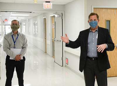 Enloe Medical Center President and CEO Mike Wiltermood, right, speaks Wednesday during a tour of the hospital's Rehabilitation Center which has been converted into a field medical station. Butte County Health Officer Dr. Andy Miller, left, joined the tour and spoke about impacts the county expects in the future. (Matt Bates -- Enterprise-Record)