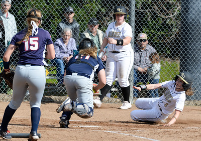 Butte College's Cambria Weintraub (right) slides into home plate as American River catcher Sam Anderson (left) goes for the tag. American River pitcher Cassie Ralston (15) looks on during the Roadrunners' home opener on Feb. 1 at Butte College. (Matt Bates -- Enterprise-Record File)