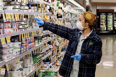 Melys Jerez, a volunteer, picks out groceries requested by a senior isolating at home at a Safeway in Chico on Tuesday. She is wearing protective medical equipment as a precaution, but public health officials are not recommending them for the general public. (Camille von Kaenel -- Enterprise-Record)