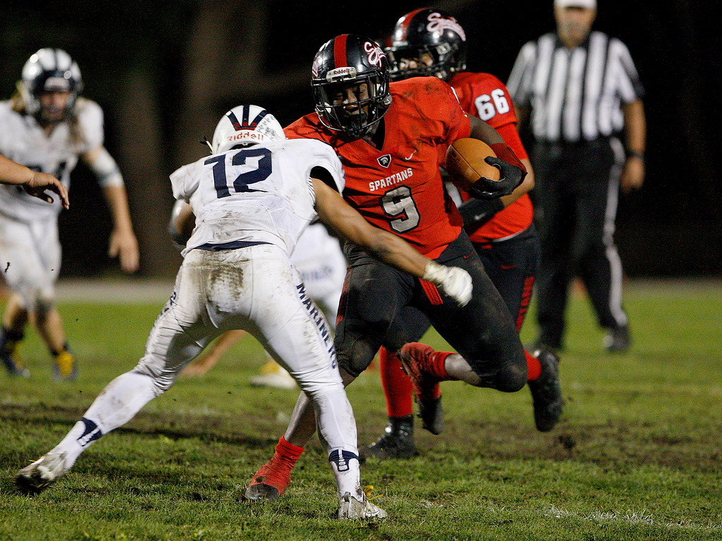 . Seaside\'s Demarcus Hawkins (9) rushes past Aptos\' Silvano Lopez (12) in the first half of their game in Seaside on Friday, Sept. 29, 2017.  (Vern Fisher - Monterey Herald)