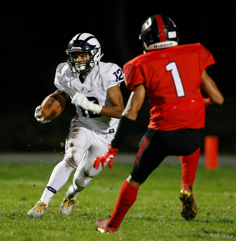 . Aptos running back Silvano Lopez (12) avoids Seaside\'s James Davis (1) in the first half of their game in Seaside on Friday, Sept. 29, 2017.  (Vern Fisher - Monterey Herald)