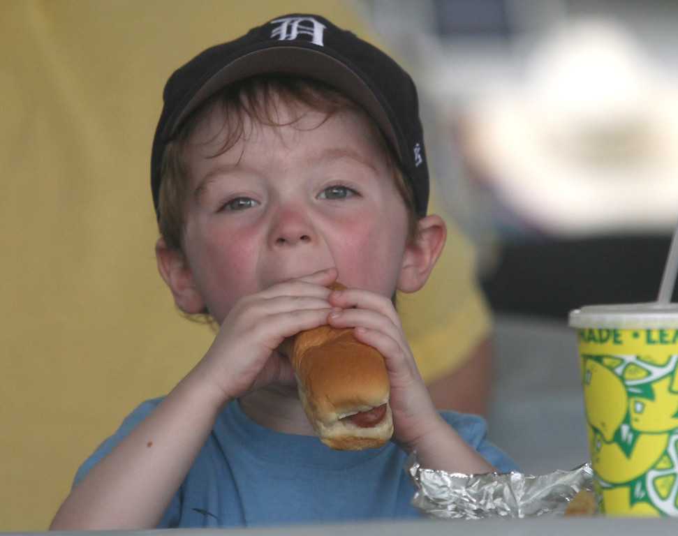 . Getting a big bite out of his hot dog is Harrison Robert. Children also got a big kick out of the Ultimate Air Dogs, who performed tricks during AquaFest in St. Clair Shores. PHOTOS BY DAVID ANGELL - FOR THE MACOMB DAILY