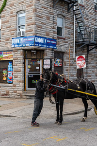 """Daeshawna Chaney waits for Todd """"Gready"""" Cornish as he buys drinks from a deli in Baltimore, Md. on May 12, 2020."""