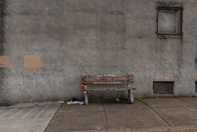 """An empty bench that reads """"Baltimore, The Greatest City in American"""" on May 12, 2020."""