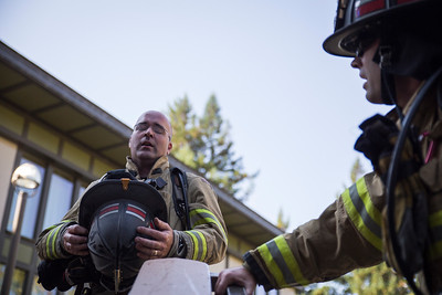 Ross McDonald takes a breath at the top of Cypress student dorms at Humboldt State. He said he was only about half way done. The fire suits they wear keep the heat in.  (Sam Armanino - Times-Standard)