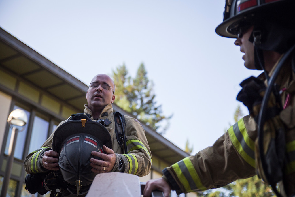 . Ross McDonald takes a breath at the top of Cypress student dorms at Humboldt State. He said he was only about half way done. The fire suits they wear keep the heat in.  (Sam Armanino - Times-Standard)